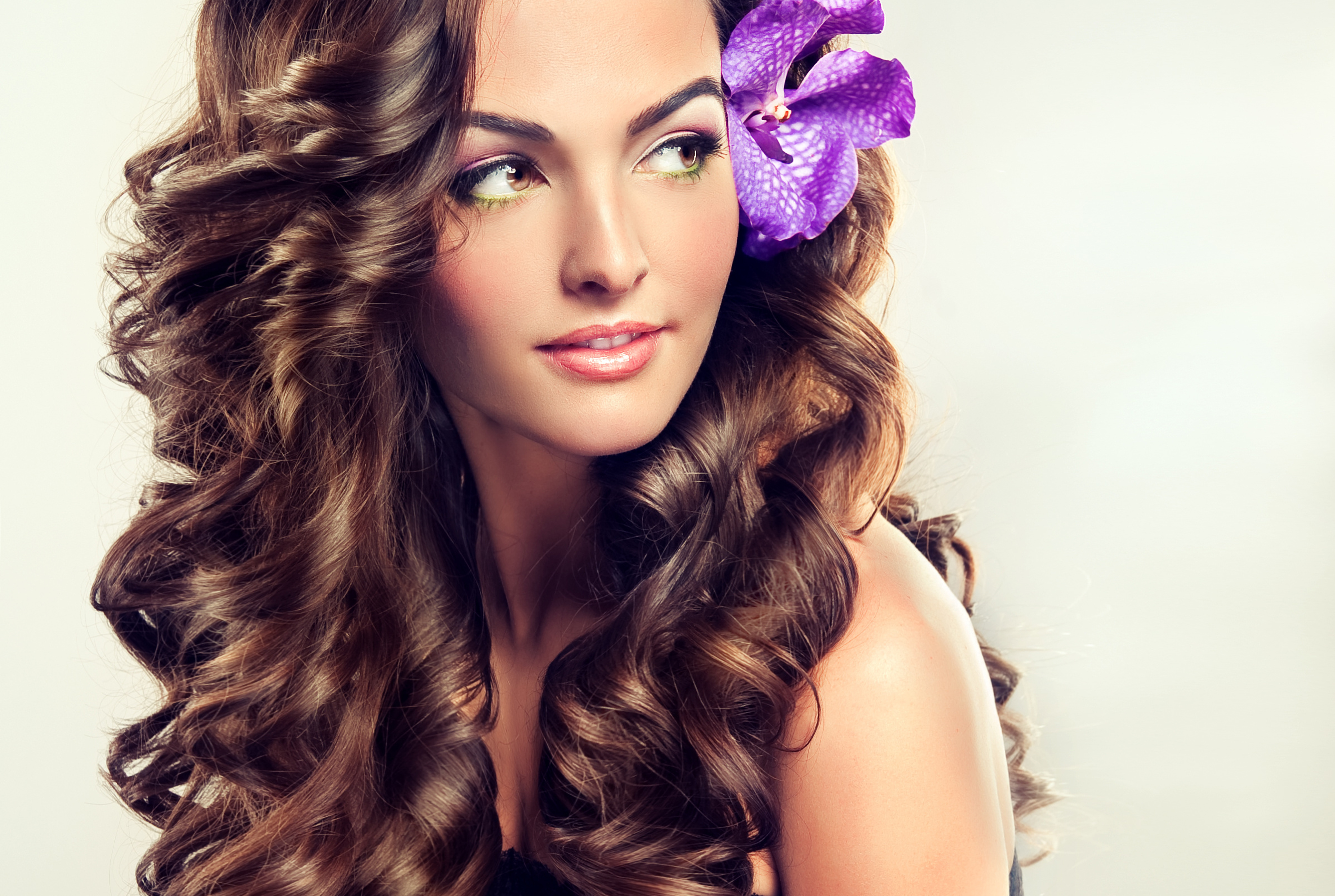 Beautiful girl with long curly brown hair , flower in hair ...